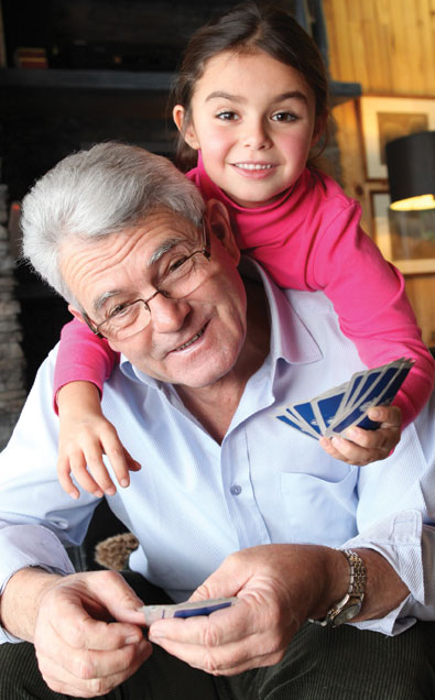 grandfather and granddaughter play cards and enjoy Autumn's Promise amenities